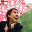 Young Woman Sheltering From Rain Under Umbrella — Stock Photo #76135451