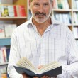 Portrait Of Male Customer Reading Book In Bookstore — Stock Photo #77136301