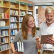 Male And Female Owners Of Bookstore Using Digital Tablet — Stock Photo #78448810