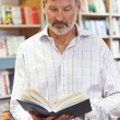 Male Customer Reading Book In Bookstore — Stock Photo #78449700