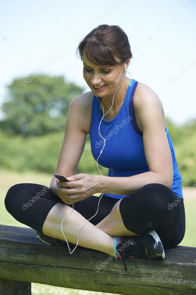 middle aged woman relaxing with mp3 player after exercise stock photo highwaystarz 93269006. Black Bedroom Furniture Sets. Home Design Ideas