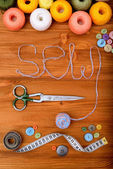 "Word ""sew"" with sewing tools and accesories on wooden background — Stock Photo"