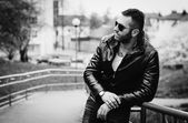 Sexy guy with attitude wearing leather jacket and sunglasses out — Stock Photo