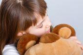 Girl  hugging her teddy bear — Stock fotografie