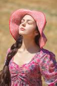 Girl in hat on wheat field — Stock Photo