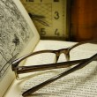 Glasses on open book on a background of the old clock. — Stock Photo #67381149