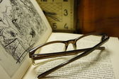 Glasses on open book on a background of the old clock. — Stock Photo