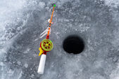 The rod for winter fishing lies near a hole — Stock Photo