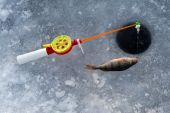 The rod for winter fishing lies near a hole — 图库照片