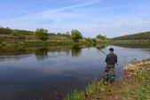 Fisherman with a fishing rod on the river — Stock Photo