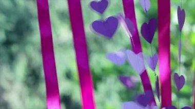 Wedding decoration, purple hearts, crimson ribbons — 图库视频影像