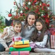 Family exchanging gifts in front of Christmas tree — Stock Photo #56696537