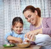 Little girl making pizza for lunch with her mother — Stock Photo