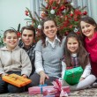 Family exchanging gifts in front of Christmas tree — Stock Photo #58150271