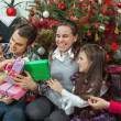 Family exchanging gifts in front of Christmas tree — Stock Photo #58150337