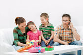Happy cheering family in white room with presents — Stock Photo