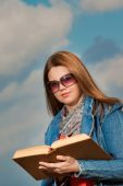 Young woman standing in summer, green park reading book — Stock Photo