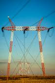Silhouette of high voltage power transmission lines and pylons a — Stock Photo