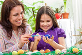 Mother and her children paint easter eggs — Stock Photo