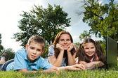 Szczęśliwa rodzina korzysta z laptopa leżąc na trawie — Zdjęcie stockowe
