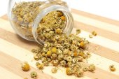 Heap of dried chamomile in glass jar — Stock Photo
