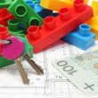 Home keys, colorful building blocks and money on housing plan — Stock Photo
