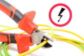 Metal pliers, green-yellow cable and high voltage danger sign — Stock Photo