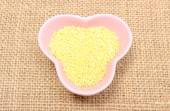 Millet groats in pink bowl on jute canvas — Stock Photo