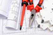 Rolled electrical diagrams, electric fuse and work tools on construction drawing of house — Stock Photo