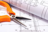 Metal pliers and rolled electrical diagram on construction drawing of house — Stock Photo