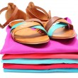 Woman sandals on pile of colorful clothes. White background — Stock Photo #53145387
