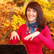Smiling woman with laptop in autumn park — Stock Photo #53700359