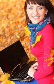 Donna sorridente con il portatile in autunno parco — Foto Stock