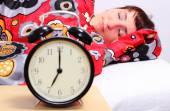 Mujer morena durmiendo en su habitación con reloj despertador — Foto de Stock
