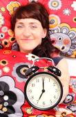 Brunette woman in her bedroom with alarm clock — Stock Photo