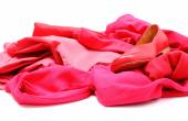 Heap of red and pink clothes with womanly shoes — Stock Photo