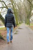 Lonely woman walking in park on cold rainy day — Stock Photo