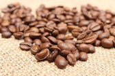 Heap of coffee on jute background — Stock Photo