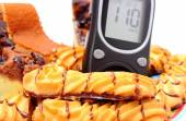 Fresh baked pastry and glucose meter. White background — Stock Photo