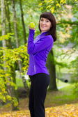 Brunette during fitness exercise with dumbbells in autumn park — Stock Photo