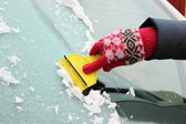 Hand of woman scraping ice from car windscreen — Stock Photo