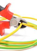 Pinzas de metal y cable verde-amarillo sobre fondo blanco — Foto de Stock