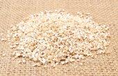 Heap of barley groats on jute canvas — Stock Photo