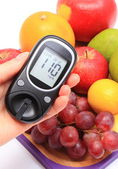 Hand of woman with glucometer and fresh fruits — Stock Photo
