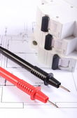 Cables of multimeter and electric fuse on construction drawing — Stock Photo
