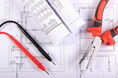 Electrical diagrams, cables of multimeter and metal pliers — Stock Photo