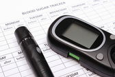 Glucometer and lancet device on empty medical forms for diabetes — Stock Photo