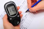 Hand of woman writing data from glucometer to medical form — ストック写真