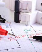 Cables of multimeter pen and electric fuse on electrical drawing — Stock Photo