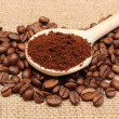 Ground coffee on wooden scoop and grains coffee — Stock Photo #61450181